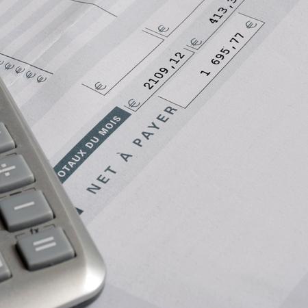 ユーロペイスリップと電卓、給与や給与の背景のためにクローズアップ、フランス語の言及ネットを支払う