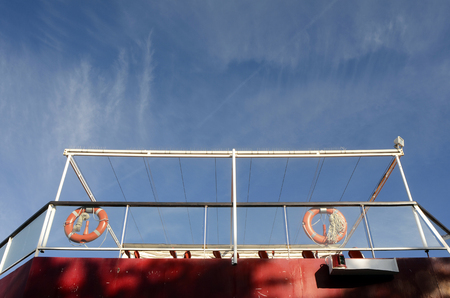 Red rescue buoys on ferry boat and blue sky