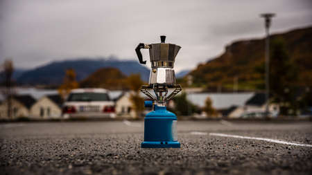 Making a coffee or tea - coffee pot during a hiking trip or camping with a camping gas stove - in a parking lot with a norwegian fjord in the background - concept of travel, freedom and adventure