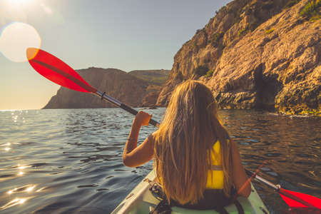 canoeing: Young woman kayaking in the sea near mountains Stock Photo