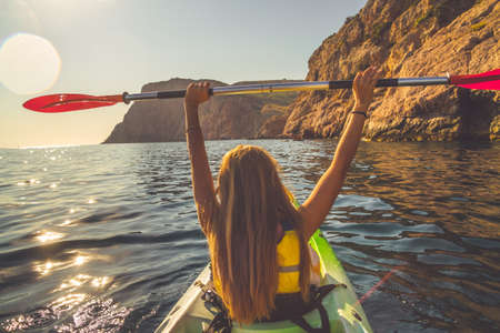 Young woman kayaking alone in the sea near mountains and holding oar over head Фото со стока