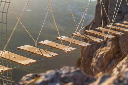 rope ladder: Wooden rope ladder over abyss in the mountains. Stock Photo