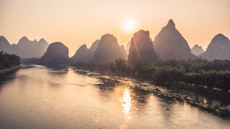 Beautiful natural landscapes of sunrise in Guilin. Mountains and River Sunrise View at famous touristic City in China Passenger Vessel floating along