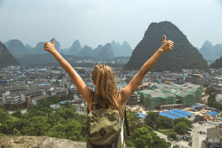 Rear view of girl with hands and thumbs up looking at the karst mountain landscape and Yangshuo city vie in famous Guilin region, China. Love travelling, freedom, adventure and exploration concept. Stock Photo