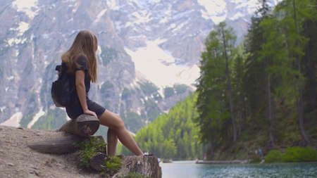 Beautiful young woman relaxing and dreaming near mountain lake. Female teenage hiker sitting on rock near Lago di Braies, Italy. Adventure,recreation and beauty in nature concept.