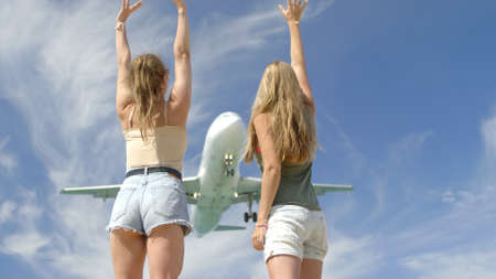 Two young joyful cheerful girls taking a selfie near airport with huge airplane flying over their heads.Best friends taking photos against sky background.Tourism,destination and friendship concept