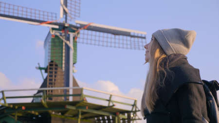 Portrait of traveller woman near old-fashioned vintage dutch windmill. Incredible cinematic low angle. Girl in beanie in front of farm mill. Excited woman travelling in autumn. Travel destination.