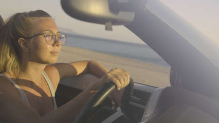 Smiling young blonde woman driving in convertible car along the coastal road in Greece. Front view of pretty hipster girl traveling and exploring the island at sunset. Dream, vacation concept. Stok Fotoğraf