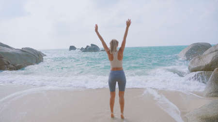Athletic woman raising hands up on the beach, feeling happy and anxious to see the ocean. Happiness, success, energy and active healthy lifestyle concept.