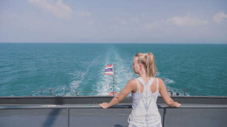 Happy blonde pretty woman standing on the ferry deck and enjoying ocean view on a warm sunny day. Thailand flag waving in the wind. Spectacular Seascape, adventure, destination, exloration concept.