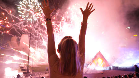 Slow motion of the silhouettes of young women watching fireworks on the holiday. Hands in the air, pretty girl having fun and dancing. Entertainment industry, recreation concept. Stok Fotoğraf