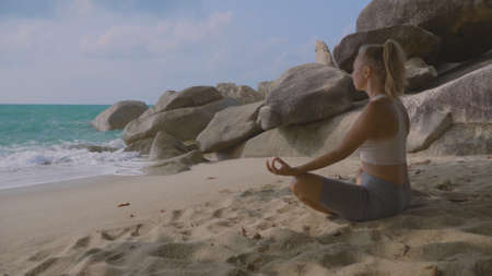 Young beautiful woman relaxing on the sunny tropical beach with stunning breathtaking view. Woman meditating in lotus pose. Vacation, recreation, travel industry and mindfulness concept.