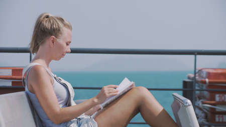 Young pretty blonde woman relaxing on the boat and reading a book. Beautiful girl reading on a ferry boat during trip on a warm sunny day. Recreation, adventure, iq and learning concept. Stok Fotoğraf