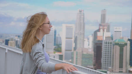Young pretty blonde woman enjoying Singapore downtown city view from a rooftop. Attractive female traveler on viewpoint, rear view. Mindfulness, adventure, travel destination and exploration concept. Banco de Imagens