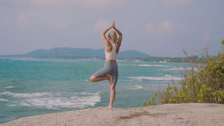 Young female practicing yoga on the beach at sunset. Pretty slim woman performs an exercise. Ecstatic young woman sitting on beach in yoga pose. Healthcare, meditaion, welness, mindfulness concept.