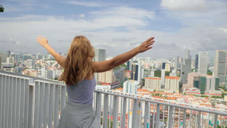 A happy tourist girl holds up her hands and enjoys the stunning view of the skyscrapers in Singapore on a warm summer day. Travel destination, adventure, success and exploration concept.