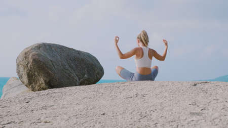 Yoga woman practices yoga and meditates in lotus position on beach sea. Healthy female girl sits in pose of lotus sukhasna meditating or practicing yoga in nature ocean outdoors, relaxing