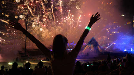 Firework streaks in night sky, celebration background. Silhouette of a young woman against illuminated sky.