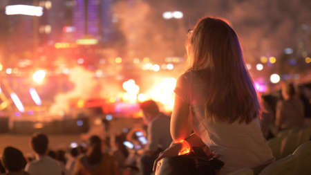silhouette of young blonde female at a concert in front of the scene in bright light with fire show outdoors. Night scene. Leisure activity, entertainment industry concept.