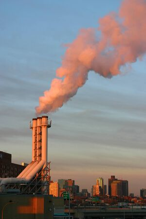 An industrail power plant pumping out smog from its smokestack into the city. photo