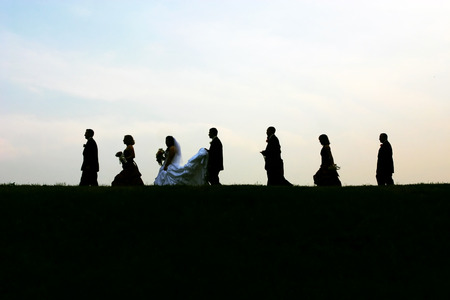 formals: Silhouettes of a modern bridal party over a blue horizon.