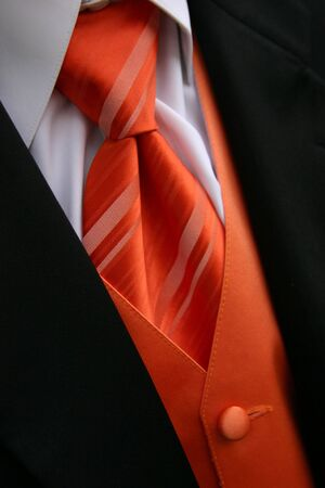 A closeup image of an orange tie, vest and tux