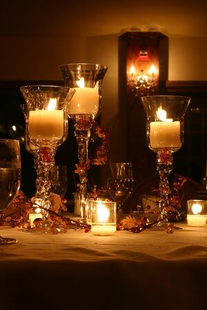 illuminated candles, vases, and glassware Stock Photo