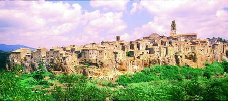 Background the hill, the cloud, the sky, the tree and the old town of Pitigliano, at the sun light. photo
