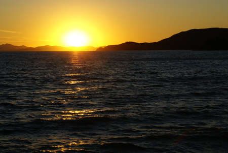 The line of the horizon where the sun goes down. A sunset in the Tyrrhenian Sea in Italy. Stock Photo