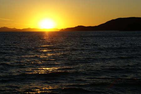 tyrrhenian: The line of the horizon where the sun goes down. A sunset in the Tyrrhenian Sea in Italy. Stock Photo