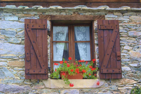 A typical chalet in the Italian Alps, with flowers and wooden facade. Stock Photo
