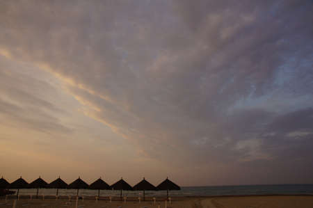 Beach at the Sunset with umbrellas