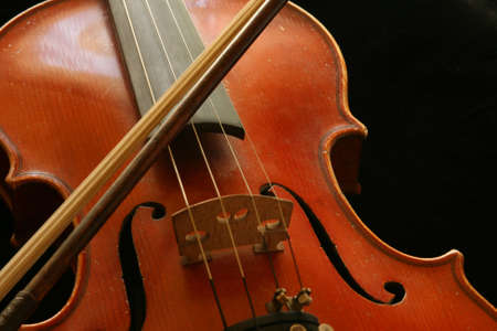 Vintage shiny violin and a bow isolated on black photo