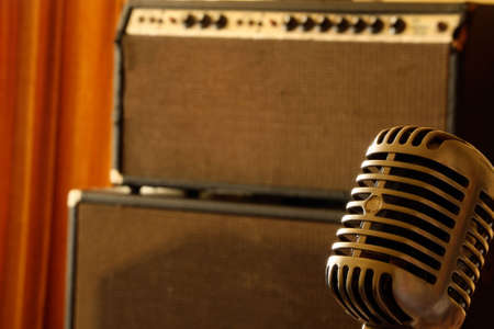 guitar amplifier: Vintage microphone standing in front of a vintage vacuum tube amplifier