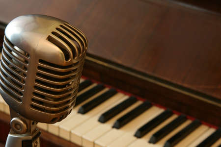 Vintage microphone and an old piano, selective focus photo