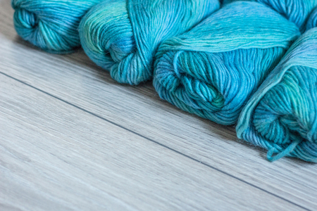 Turquoise, green and and blue yarn skeins are lying next to each other