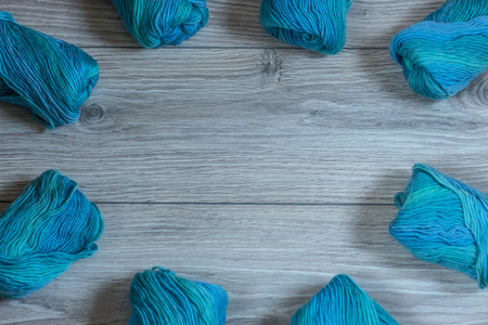 Many yarns balls on a wooden background arranged in a circle shape