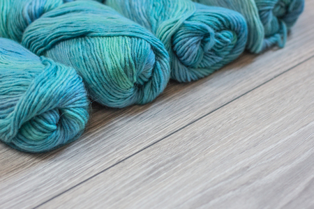 Composition of several skeins of yarns that are lying on a grey wooden background. The combination of blue, green and turquoise form a very beautiful modern colour scheme. Great background for advertisements or social networks, both for print and web