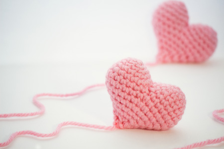 Crochet heart handmade from a pink thick wool yarn.The thread is not cut and still attached to the heart.