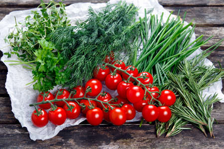 heathy diet: Fresh Tomatoes and Green Vegetables.  Dill, Rosemary, Parsley, Chives and thyme. on old wooden table.