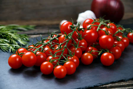 heathy diet: Fresh Tomatoes and Green Vegetables. Onion, Rosemary, garlic on on a stone board.