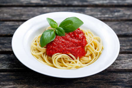 Spaghetti with marinara sauce and basil leaves on top, on wooden table