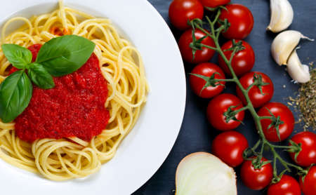 marinara sauce: Spaghetti with marinara sauce and basil leaves on top, decorated with cherry tomatoes, garlic, onion, Italian herbs mix  on blue background. Stock Photo