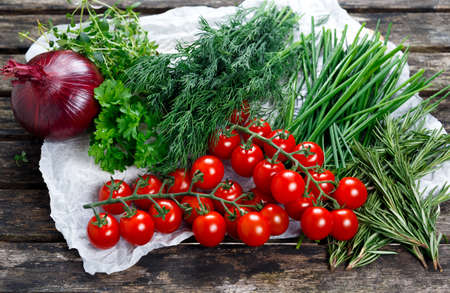 heathy diet: Fresh Tomatoes and Green Vegetables. Onion, Dill, Rosemary, Parsley, Chives and thyme. on old wooden table