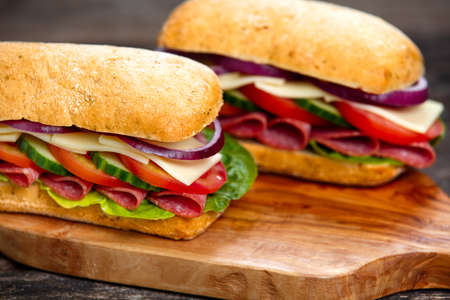 Sandwich with lettuce, slices of fresh tomatoes, cucumber, red onion, salami and cheese. Stock Photo