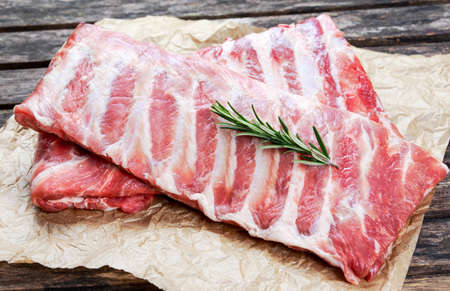Raw  Pork ribs with a rosemary. on crumpled paper. Stock Photo