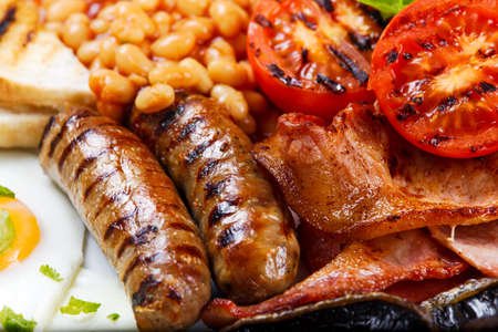 Full English breakfast with bacon, sausage, fried egg, baked beans and mushrooms.