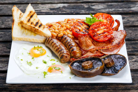 english breakfast: Full English breakfast with bacon, sausage, fried egg, baked beans and mushrooms.