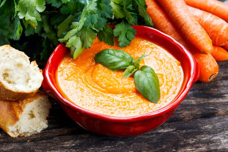 slurp: Carrot cream soup with vegetables and basil Stock Photo