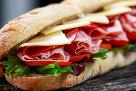 Broodje met sla, plakken van verse tomaten, salami, brom en kaas Stockfoto